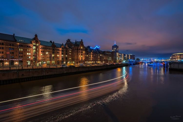 Light trails on river against buildings at dusk