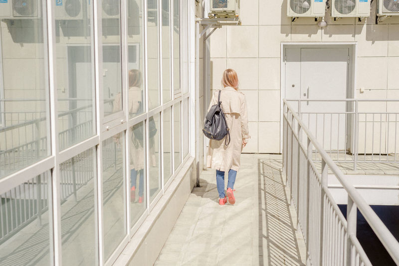 Rear view of young woman with backpack walking in corridor