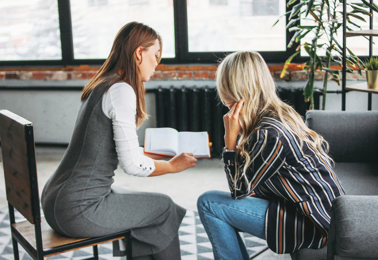 Colleagues discussing while sitting in office
