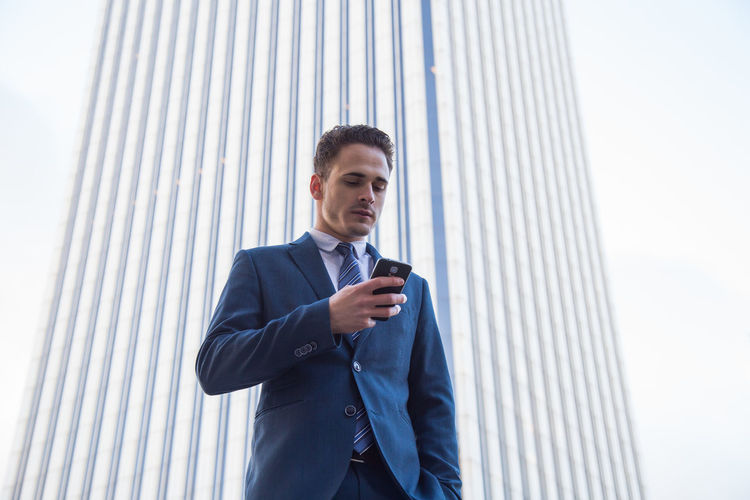 Low Angle View Of Businessman Using Phone Against Wall