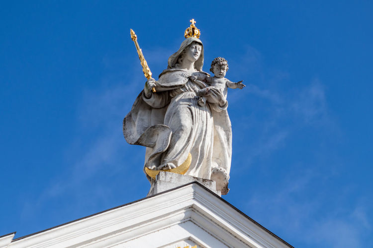 Statue with golden scepter and crown on st. stephen's cathedral in passau, bavaria, germany