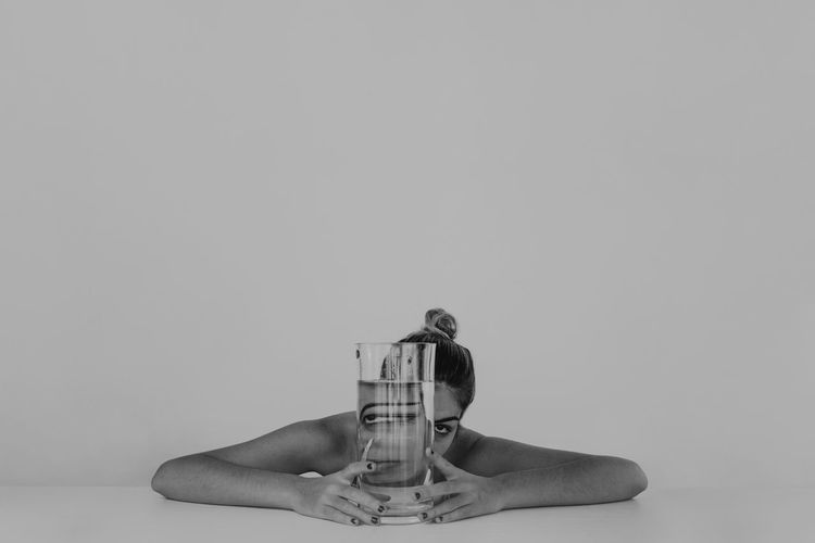Portrait Of Young Woman With Drinking Water Against White Background