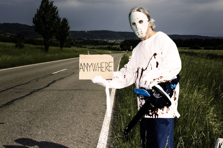 Psychopath with chainsaw hitching a ride to anywhere. Blood Chainsaw Conceptual Hitchhiker Hitchhiking Holding Humour Killer Mask Men Murderer One Person People Psycho Psychopath Road Serial Killer Sign Ski Mask Standing Straightjacket Street