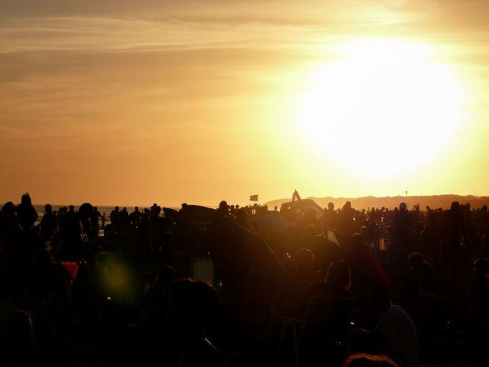 Silhouette people at music concert against sky during sunset
