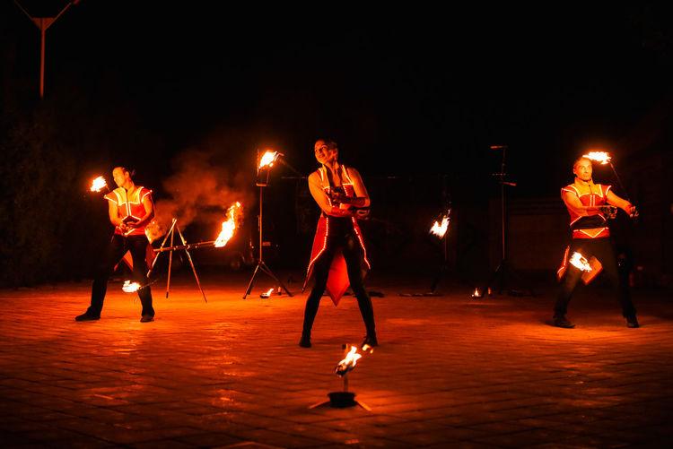 People at illuminated music concert at night