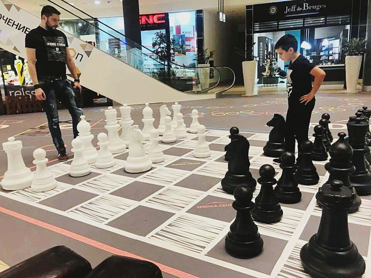 leisure games, game, chess, board game, leisure activity, chess piece, strategy, relaxation, chess board, men, real people, arts culture and entertainment, people, full length, playing, incidental people, sport, competition, standing, lifestyles, pawn - chess piece