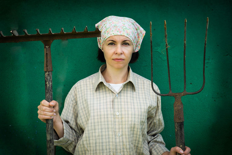 Portrait of woman holding gardening equipment while standing against wall