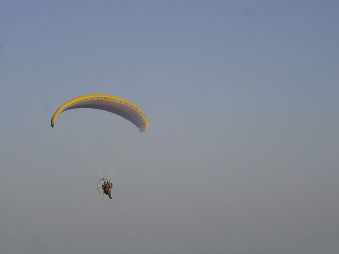 Low angle view of hang-gliding against clear sky