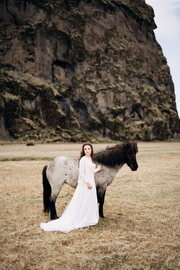 Woman with horse standing on field against rock formation