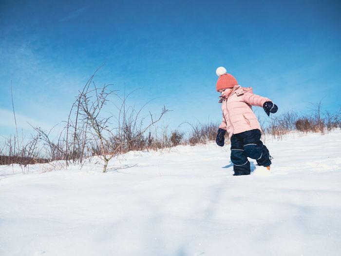 Rear view of boy on snow field against sky