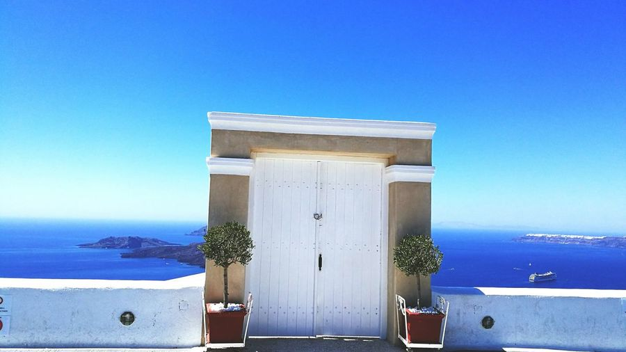 Door on terrace by sea against clear sky