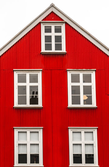 White house window on red wall of building