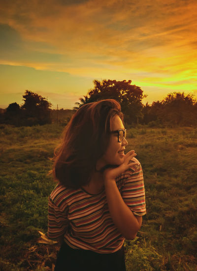 Beautiful woman standing on field against sky during sunset