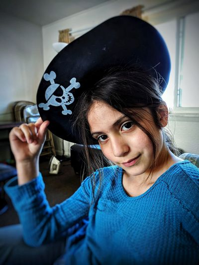 Portrait of girl wearing pirate hat at home