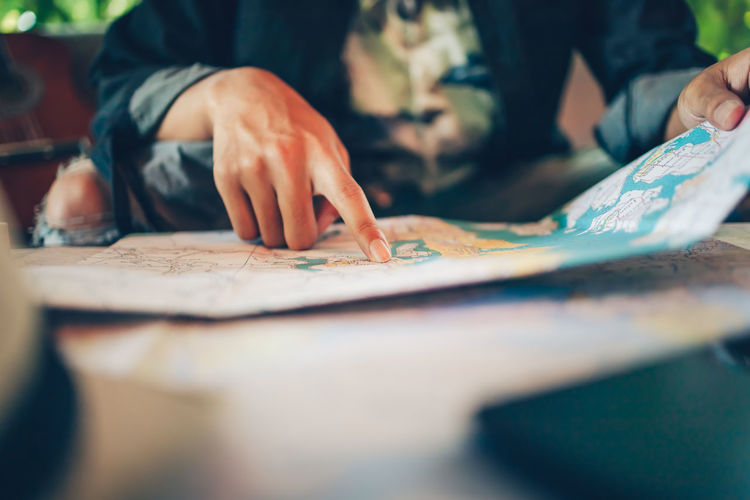 Midsection of man looking at map on table