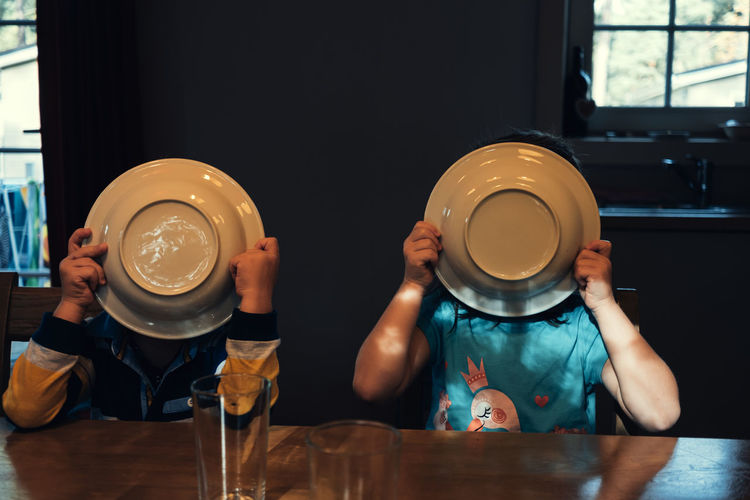 Siblings covering face with plates while sitting by table at home