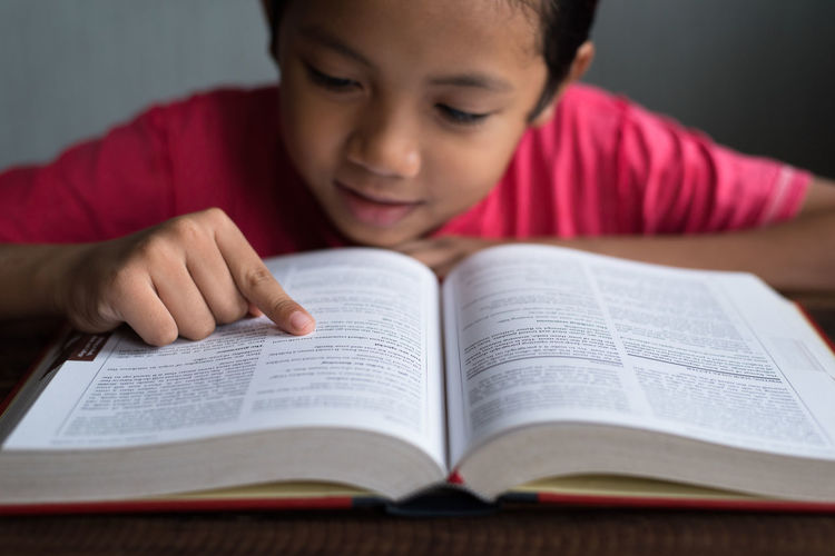 boy reading book Asian  Reading Book Boy Childhood Close-up Day Education Front View Hand Headshot Indoors  Learning Malaysian One Person Pointing Real People School Studying