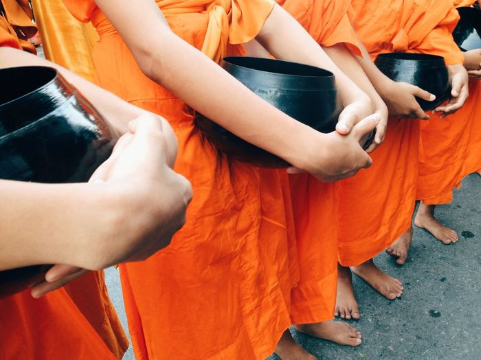 Midsection Of Monks Holding Container While Standing In Shrine