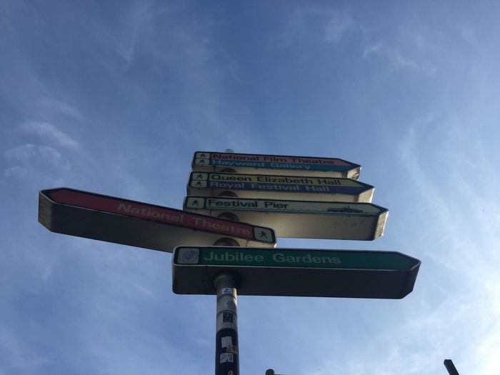 Low Angle View Of Road Signs Against Blue Sky