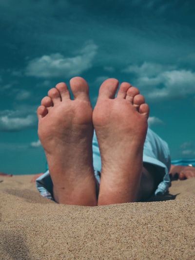 Low section of person relaxing on beach