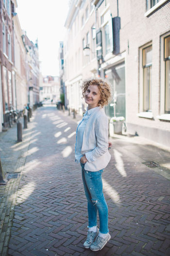 Portrait of smiling woman standing on footpath amidst buildings