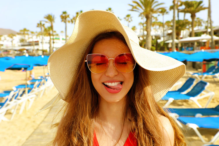 Smiling Young Woman Wearing Sunglasses At Beach