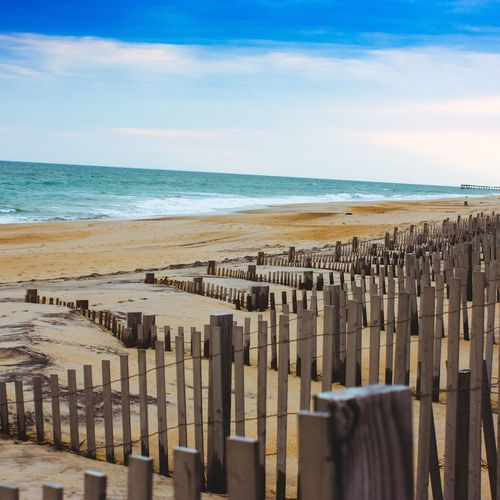 Wooden fence at beach against sky