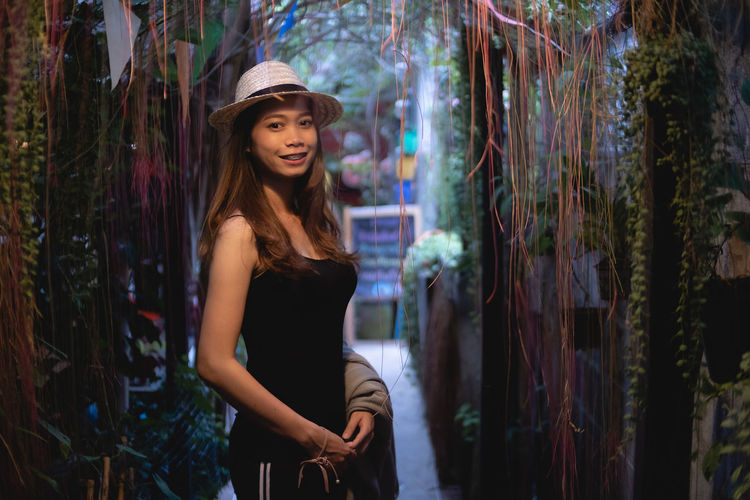 Portrait of smiling woman wearing hat standing amidst creeper plant