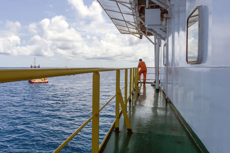 Offshore man Corridor Industry Coveralls Upstream Oilfield Oil And Gas Installation Construction Offshore Man Work Corridor Barge Accommodation Ocean Sea Oilfield Tugboat Anchor Cloudy Horizon Over Water Handrail  Perspective Water Men Standing Cloud - Sky Boat Seascape Wave