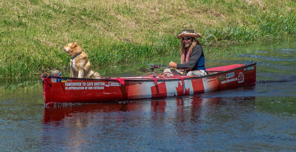 Men sitting on boat moored at riverbank