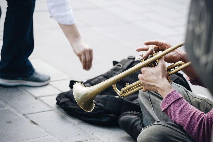Low Section Of Man Giving Money To Street Musician Playing Trumpet At Footpath In City