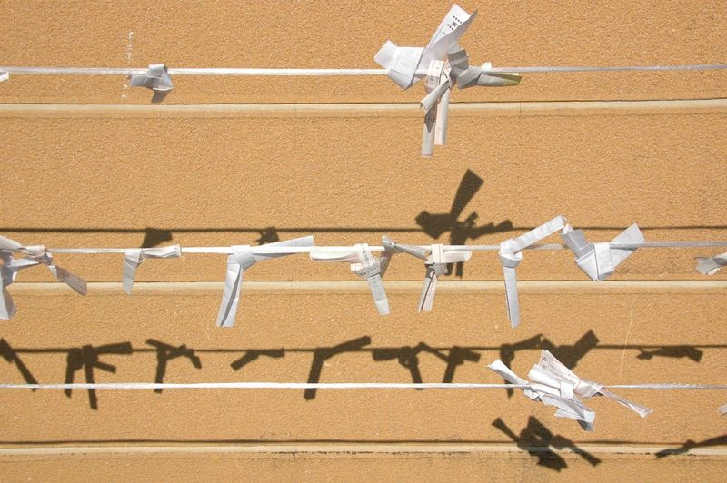 Fortune papers tied on ropes against wall during sunny day
