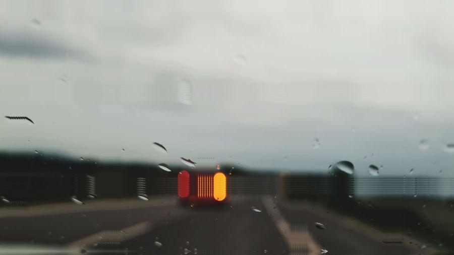 Road seen through wet glass window