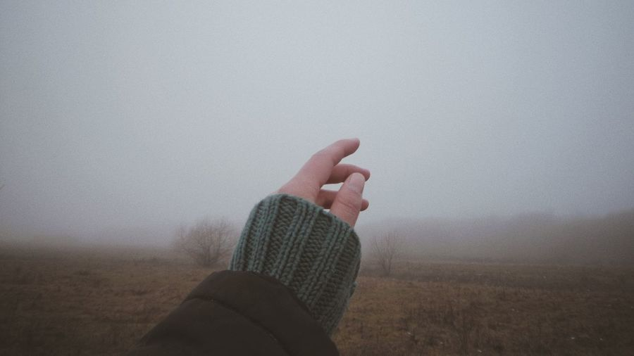Midsection of person on field against sky during foggy weather