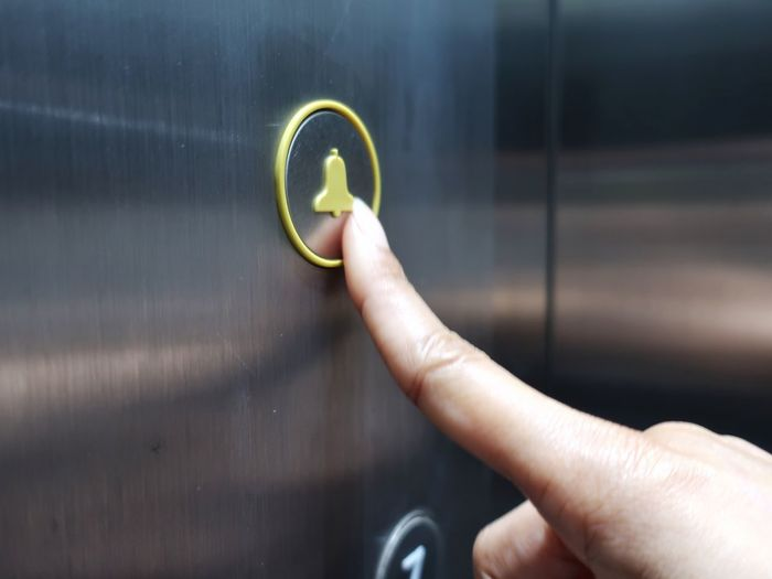 Cropped Image Of Hand Pressing Button In Elevator