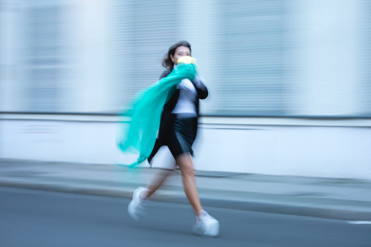 Woman holding scarf running on road in city
