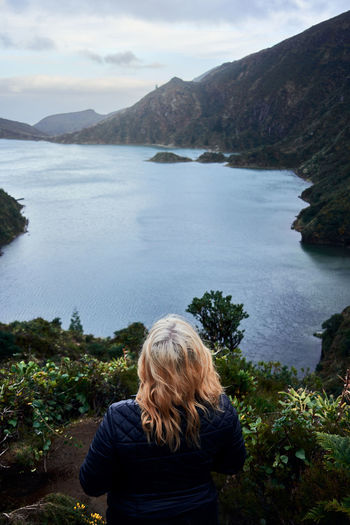 Rear view of woman looking at lake against mountain