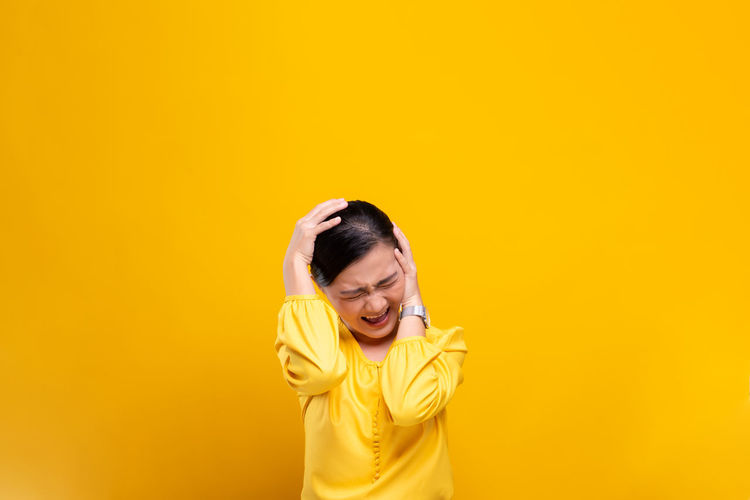 Woman with headache standing against yellow background