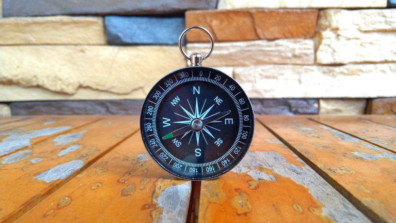 Close-Up Of Compass On Wooden Table Against Wall