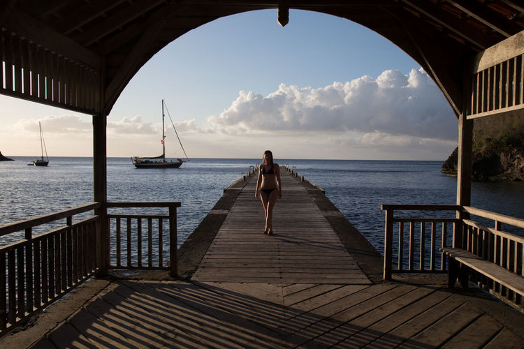 Woman in bikini walking on pier over sea seen from gazebo