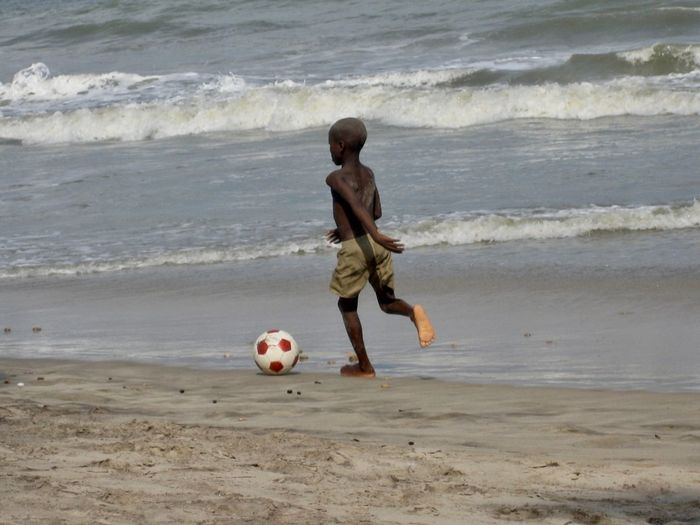 Full length of shirtless boy playing soccer on shore at beach