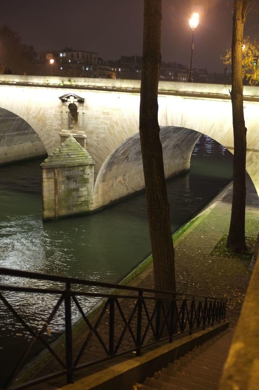 BRIDGE OVER RIVER AGAINST ILLUMINATED LIGHTS AT NIGHT