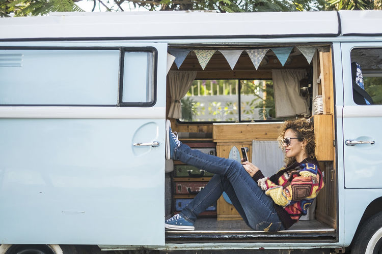 Side View Of Smiling Woman Using Phone While Sitting Camper Van
