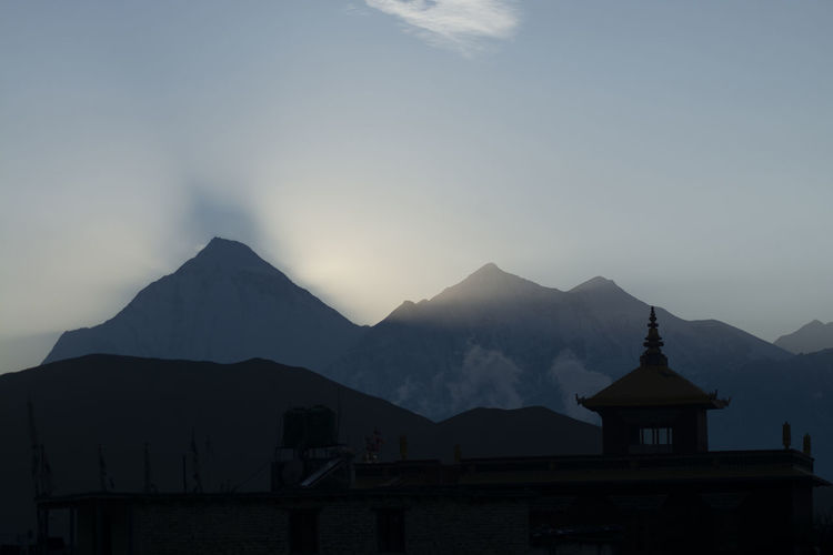 Silhouette building and mountains against sky