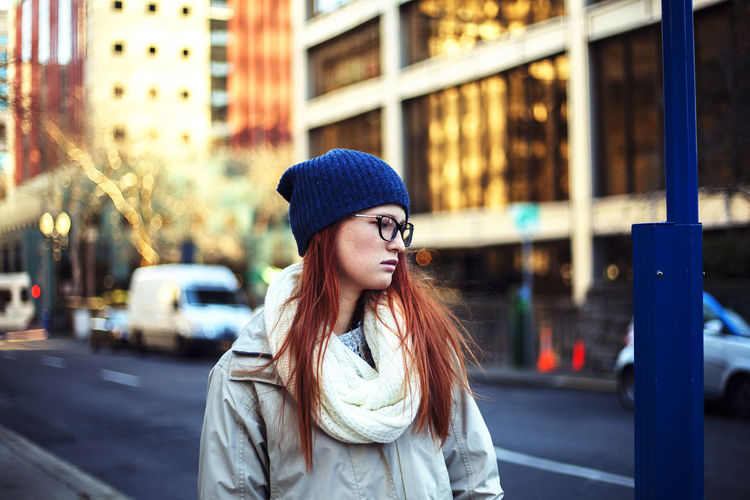Thoughtful woman wearing knit hat while standing on street in city