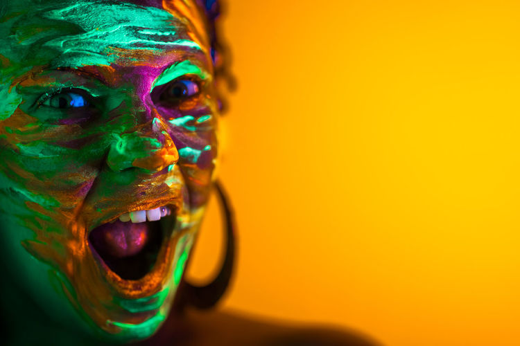 Portrait of girl with fluorescent paint makeup. Dye glowing near UV light. Woman with open mouth in neon light. Night club, party, halloween psychedelic concepts Multi Colored Portrait One Person Face Paint Paint Headshot Close-up Indoors  Human Body Part Enjoyment Copy Space Fun Celebration Emotion Happiness Looking At Camera Yellow Studio Shot Human Face Body Part Mouth Open Holi Neon