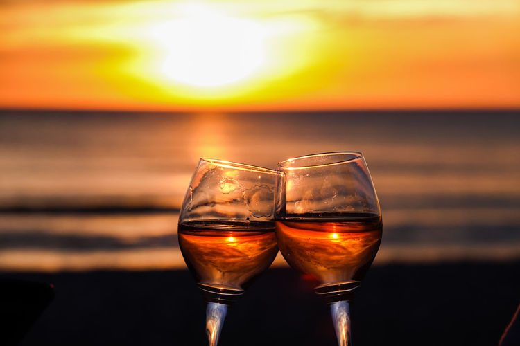 Close-up of beer glass on beach against sky during sunset