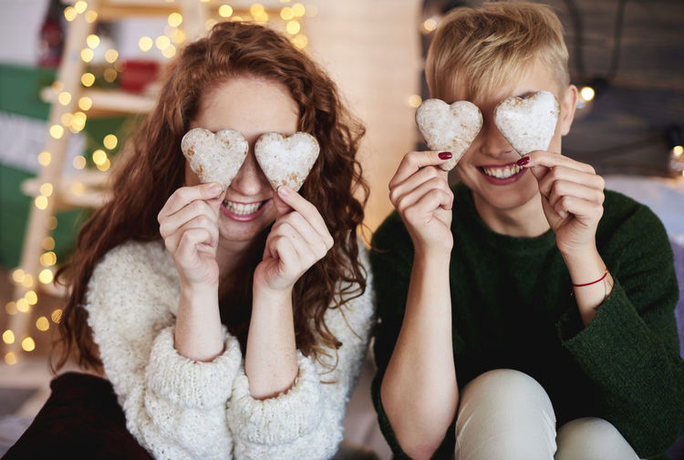Cheerful Sisters Holding Heart Shape Cookies At Home