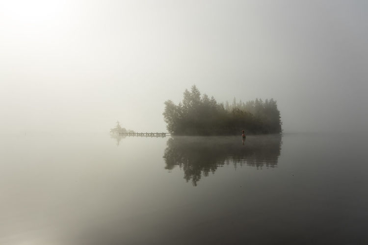 Scenic view of lake against sky at foggy weather