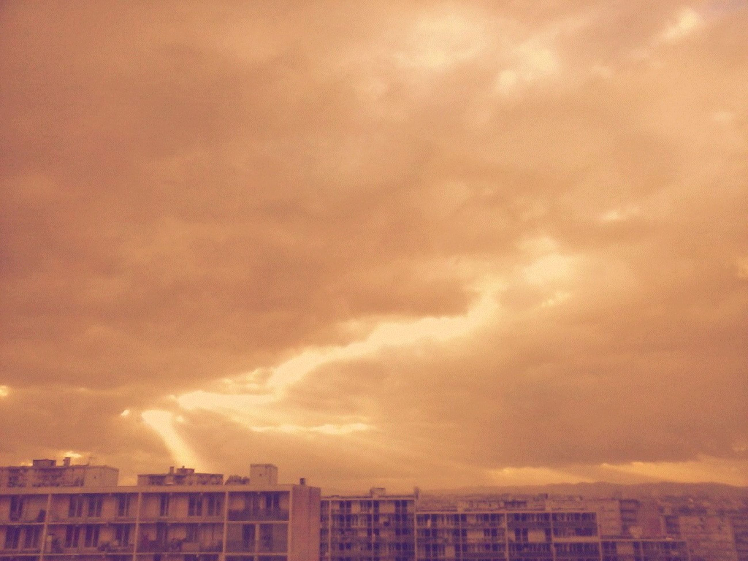 building exterior, architecture, built structure, cloud - sky, sky, sunset, cloudy, weather, city, overcast, low angle view, orange color, cloud, residential building, building, residential structure, dramatic sky, storm cloud, outdoors, nature